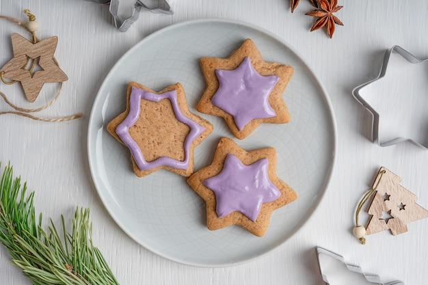 Portion von herzhaften lebkuchenplätzchen mit violettem zuckerguss serviert auf grauem teller auf weißem holztisch