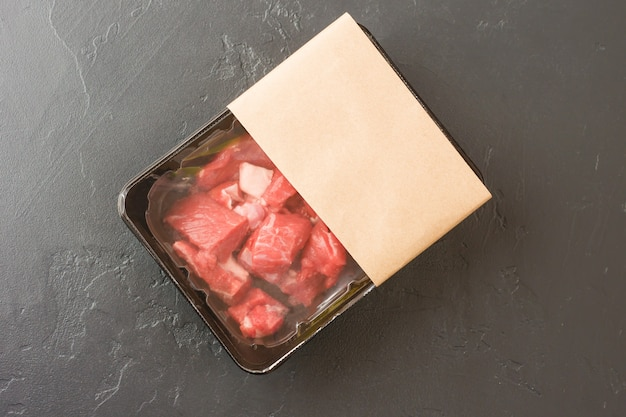 Portionierte frischfleischstücke in vakuumverpackung auf schwarzem hintergrund. ansicht von oben. logo-layout-design. das konzept des schnellen kochens.