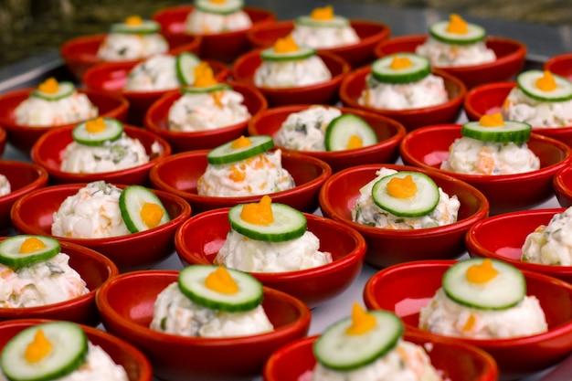Portionsalat mit mayonnaise in einer roten platte, verziert mit einem stück gurke