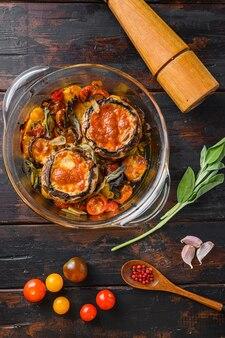 Portobello gebacken mit cheddar-käse, kirschtomaten und salbei im glastopf auf alter hölzerner hintergrundoberansicht.
