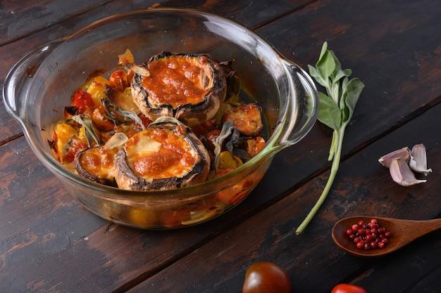 Portobello-pilze, gebacken mit cheddar-käse, kirschtomaten und salbei im glastopf auf seitenansicht des alten hölzernen hintergrunds.