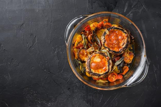 Portobello-pilze, gebacken mit cheddar-käse, kirschtomaten und salbei im glastopf