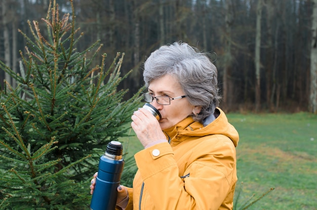 Porträt ältere frau draußen im wald. ältere frau, die heißen tee während des gehens trinkt. konzeptwanderung, wärmendes getränk bei kaltem wetter.