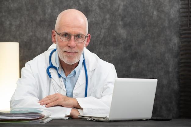Porträt älteren doktors sitzend im ärztlichen dienst