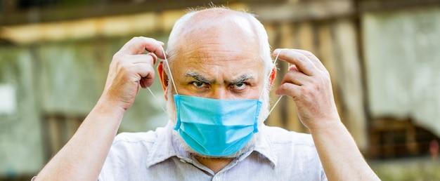 Porträt alter mann in einem chirurgischen verband, coronavirus, medizinische maske. alter mann, der gesichtsmaske trägt.