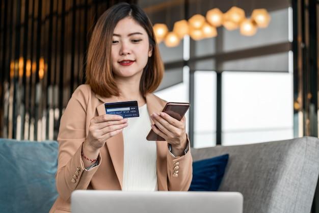 Porträt-asiatin, die kreditkarte mit handy, laptop für das on-line-einkaufen in der modernen lobby oder im arbeitsplatz, in der kaffeetasse, in der technologiegeldgeldbörse und im online-zahlungskonzept, im kreditkartenmodell verwendet