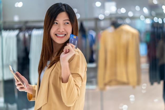 Porträt-asiatin, die kreditkarte mit intelligentem handy für das on-line-einkaufen im kaufhaus über der kleidungsshop-speicherwand, der technologiegeldbörse und dem online-zahlungskonzept verwendet