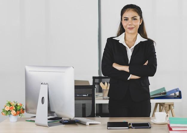 Porträt asiatische erwachsene frau ist büroleute, die anzug tragen und ihre 2 hände auf den arbeitstisch legen und kamerablick zu selbstbewusstem und lächelndem blick mit einem lächeln im gesicht betrachten.