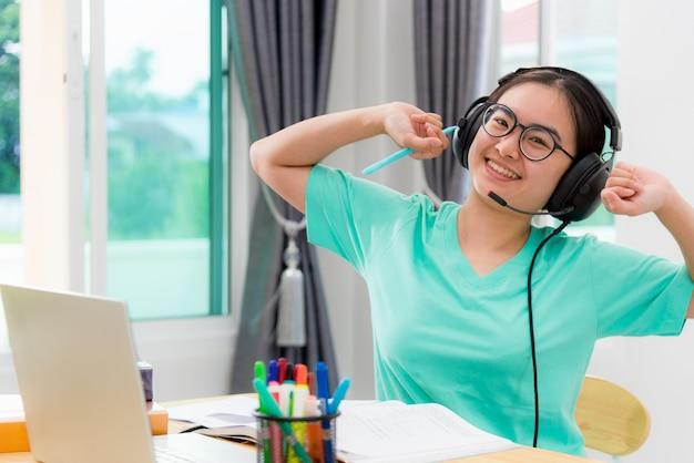 Porträt asiatische junge studentin brille kopfhörer strecken sich vom studium online-klasse college-lernen internet-bildung lächeln nachschlagen teenager-mädchen arbeitsabstand auf laptop-computer zu hause