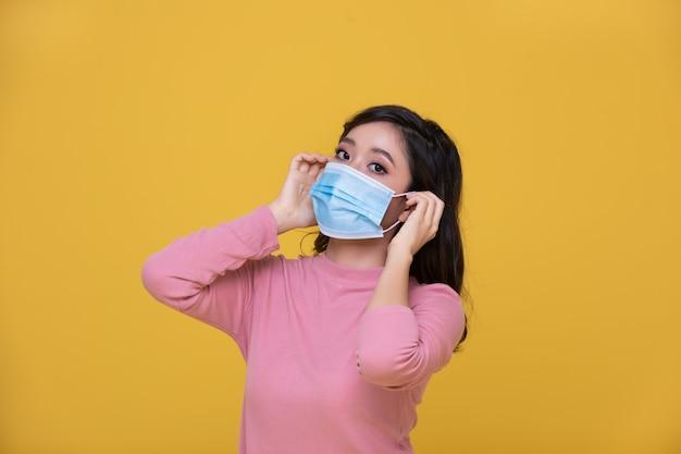 Porträt asiatische schöne glückliche junge frau, die gesichtsmaske oder schutzmaske gegen coronavirus-krise oder covid-19-ausbruch auf gelbem hintergrund trägt