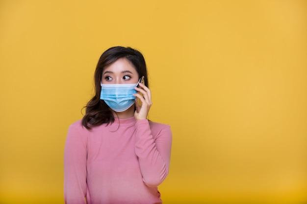 Porträt asiatische schöne glückliche junge frau, die gesichtsmaske oder schutzmaske gegen coronavirus-krise oder covid-19-ausbruch trägt und sie handy oder smartphone auf gelbem hintergrund verwendet