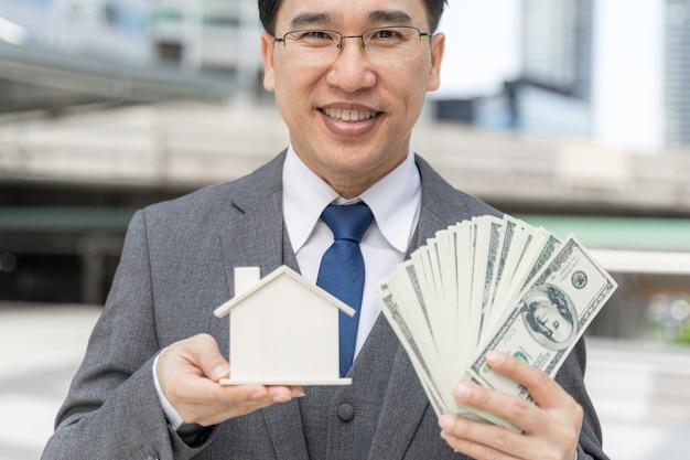 Porträt asiatischer geschäftsmann, der geld uns dollarnoten und modellhaus auf geschäftsviertel hält