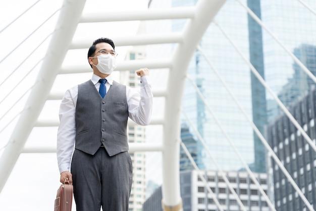 Porträt asiatischer geschäftsmann, der schützende gesichtsmaske zum schutz während der quarantäne trägt