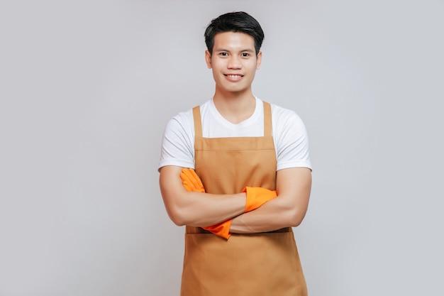 Porträt asiatischer junger gutaussehender mann steht mit verschränkten armen, er trägt schürze und gummihandschuhe, lächelt und schaut zur kamera, kopierraum
