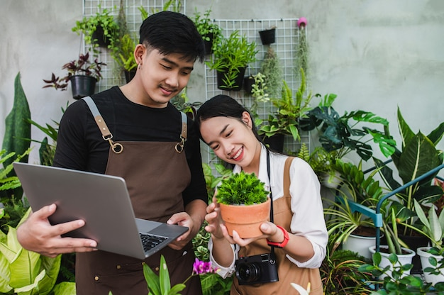 Porträt asiatisches junges gärtnerpaar mit schürze verwendet gartengeräte und laptop, um die zimmerpflanzen im gewächshaus zu erforschen und zu pflegen