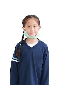 Porträt asiatisches kleines kindermädchen, das medizinische gesichtsmaske trägt, die auf ihrem kinn lokalisiert auf weißem hintergrund geschleudert wird. inmitten des covid-19-pandemie-konzepts