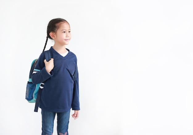 Porträt asiatisches kleines kindermädchen in lässiger schuluniform mit rucksack lokalisiert auf weiß