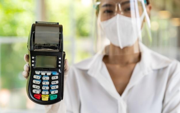 Porträt attraktive asiatische kellnerin tragen gesichtsmaske und gesichtsschutz halten kreditkartenleser für kontaktlose zahlung mit innenrestaurant hintergrund. neues normales kontaktloses zahlungskonzept für restaurants.