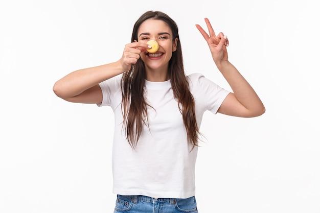 Porträt ausdrucksstarke junge frau, die leckere zwei macarons über augen hält