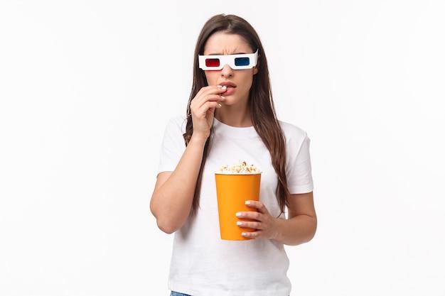 Porträt ausdrucksstarke junge frau, die popcorn isst und 3d-brille trägt