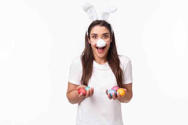 Porträt ausdrucksstarke junge frau tragen hasenohren und nase, halten farbige eier