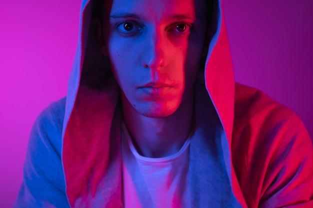Porträt ausdrucksstarker junger mann, der die kamera mit rotem und blauem licht betrachtet.