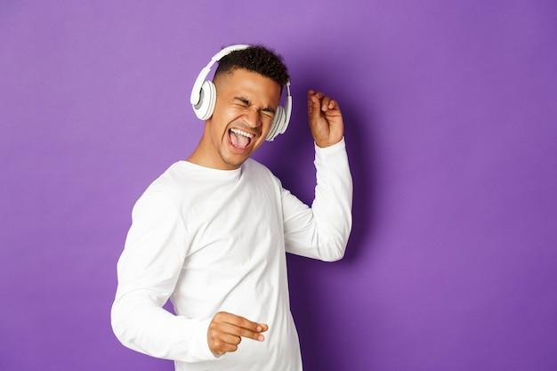 Porträt ausdrucksstarker junger mann, der musik hört