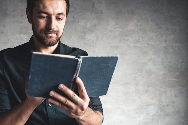 Porträt bärtiger mann, der schwarzes hemd trägt, buch liest und sich entspannt. bildung, lesen, lernen, hobbys