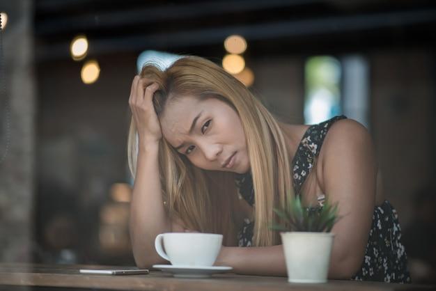 Porträt betonte die traurige junge frau, die am café sitzt