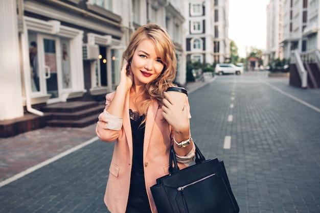 Porträt blondes modell mit langen haaren, die mit kaffee in der korallenjacke auf straße gehen. sie hat weinige lippen
