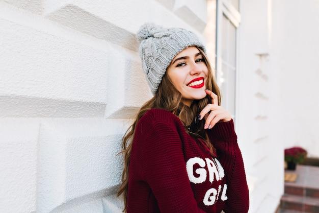 Porträt brünettes mädchen mit langen haaren im winterpullover auf grauer wand auf straße. sie trägt eine strickmütze, berührt das gesicht und lächelt.