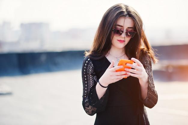 Porträt brunettemädchen mit den roten lippen und orange handy an den händen, ein schwarzes kleid tragend, sonnenbrille warf auf dem dach auf