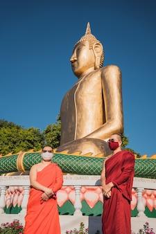Porträt buddhistischer mönche mit schutzmasken in covid-19-zeiten, in der nähe von buddha.