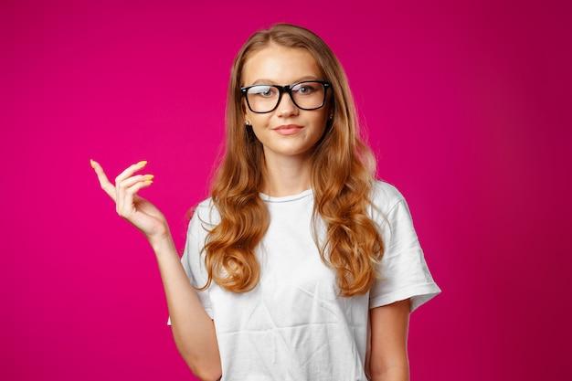 Porträt charmantes hübsches fröhliches mädchen, das kopienraum mit ihrem finger zeigt