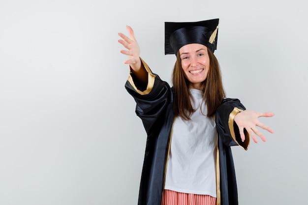 Porträt der absolventin, die arme für umarmung in freizeitkleidung, uniform und fröhlicher vorderansicht öffnet
