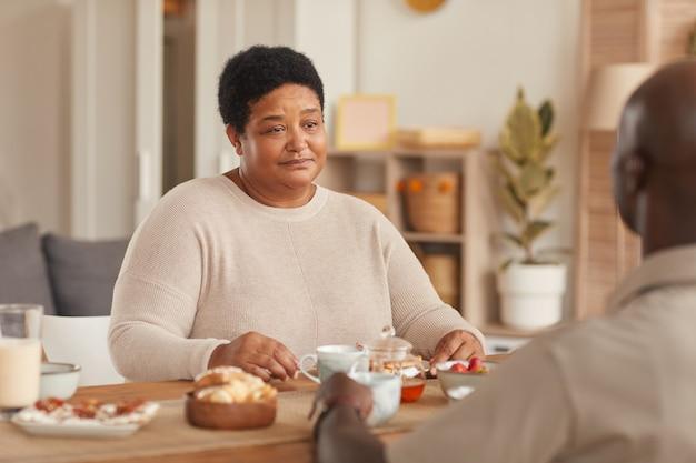 Porträt der älteren afroamerikanischen frau, die am esstisch während des frühstücks mit der familie zu hause sitzt