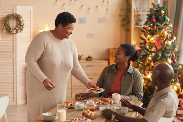 Porträt der älteren afroamerikanischen frau, die hausgemachtes essen für familie beim frühstück dient und glücklich lächelt