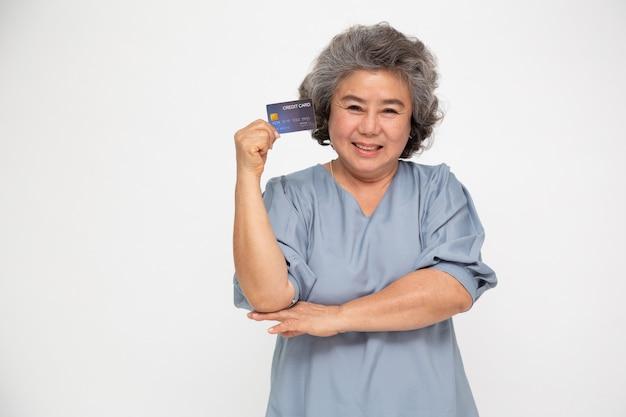 Porträt der älteren asiatischen frau, die kreditkarte hält und zur hand zeigt