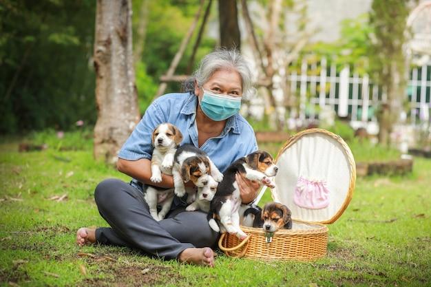 Porträt der älteren asiatischen frau mit schutzmaske und mit ihrem hündchen, das am park spielt.