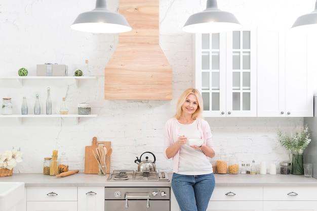 Porträt der älteren frau aufwerfend in der küche