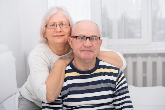 Porträt der älteren frau, die älteren mann zu hause umarmt