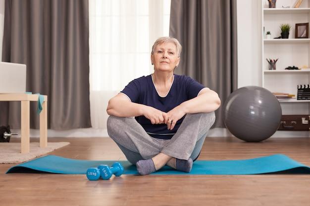 Porträt der älteren frau, die auf yogamatte sitzt.