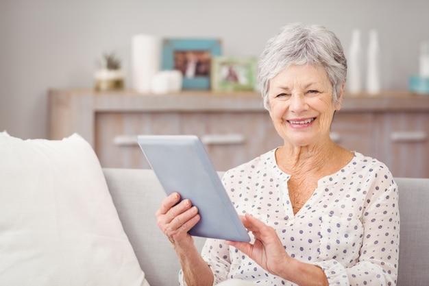 Porträt der älteren frau, die digitale tablette verwendet