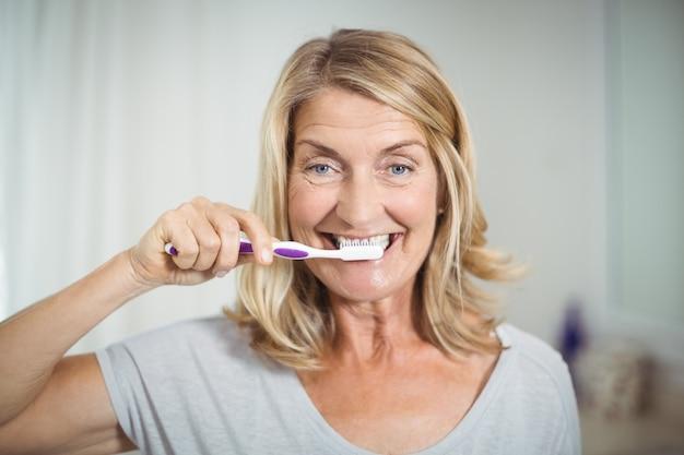 Porträt der älteren frau, die ihre zähne im badezimmer putzt
