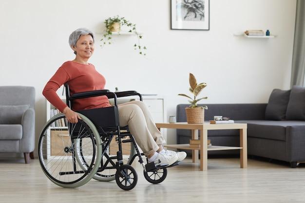 Porträt der älteren frau, die im rollstuhl sitzt und im wohnzimmer zu hause lächelt