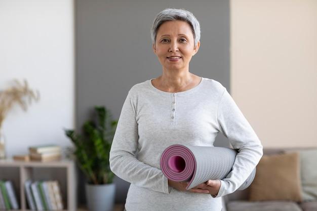 Porträt der älteren frau, die yogamatte hält