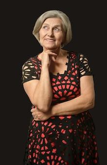 Porträt der älteren frau im kleid auf schwarzem hintergrund