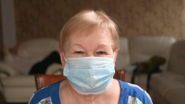Porträt der älteren frau in einer gesichtsschutzmaske, nahaufnahme. leben während einer pandemie und quarantäne
