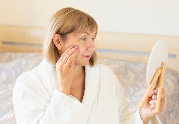 Porträt der älteren frau in ihrem schlafzimmer. konzept anti-aging, gesundheitswesen und kosmetologie, alter, rentner und reife