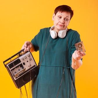 Porträt der älteren frau kassettenrecorder halten